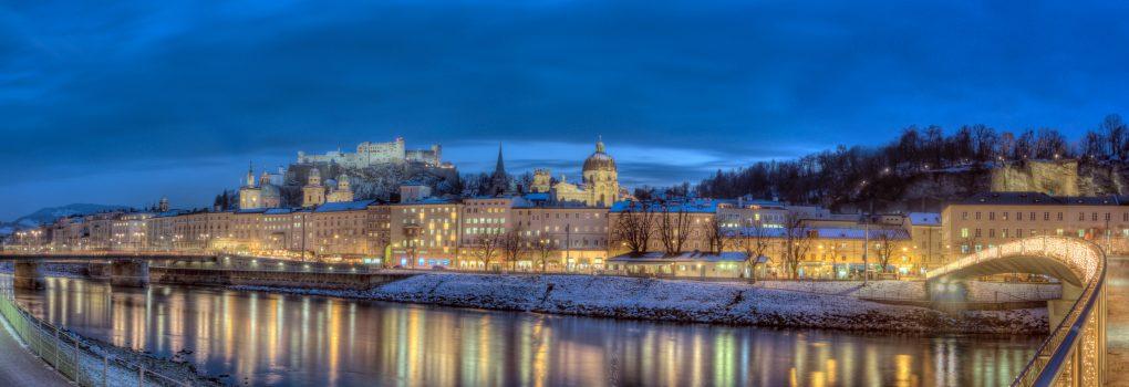 Blick auf die Altstadt von Salzburg im Winter/Advent. (inkl. Kollegienkirche, Salzburger Dom und Festung Hohensalzburg) Salzach im Vordergrund. Advent-Beleuchtung am Markatsteg rechts.  View over the historic city center of Salzburg and the Salzach river in winter/advent.